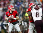 Georgia quarterback Jake Fromm (11) looks for a receiver as offensive lineman Isaiah Wilson (79) blocks Texas A&M defensive lineman DeMarvin Leal (8) in the first half of an NCAA college football game Saturday, Nov. 23, 2019, in Athens, Ga. (AP Photo/John Bazemore)