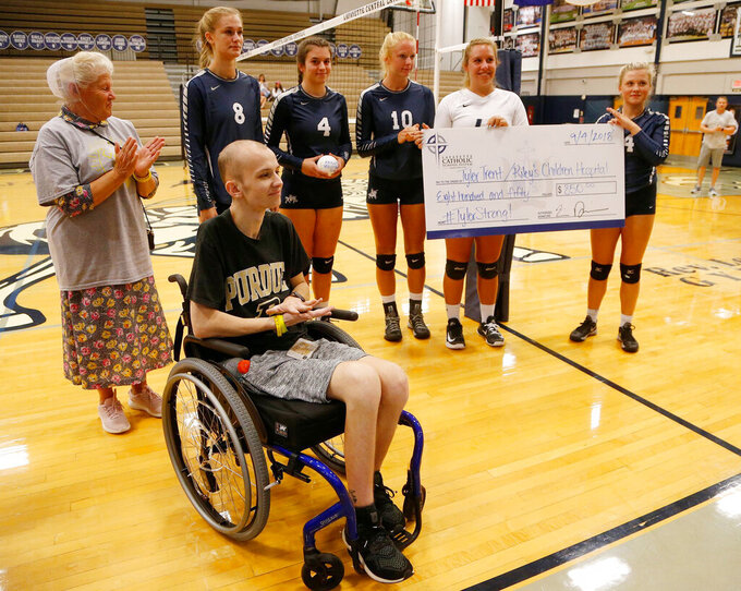 FILE - In this Sept. 4, 2018, file photo, Central Catholic players present Tyler Trent, foreground, with a check to benefit Riley Children's Hospital before meeting Lafayette Jeff in a high school volleyball game in Lafayette, Ind. A memorial gate leading to the student section entrance of Purdue University's football stadium will be built to honor Trent, the school's superfan and cancer activist who died in January. (John Terhune/Journal & Courier via AP, File)