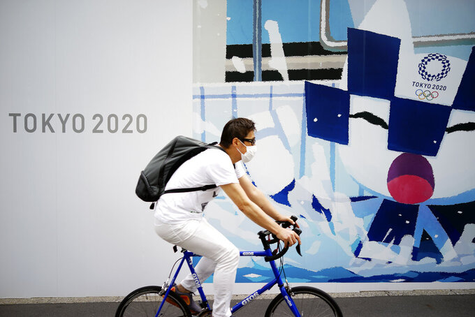 A man wearing a face mask to help curb the spread of the coronavirus rides a bicycle in front of an advertisement of Tokyo 2020 Olympic Games in Tokyo Tuesday, May 12, 2020. Japan is still under a coronavirus state of emergency, which was extended this week until the end of May, though there have been no hard lockdowns. (AP Photo/Eugene Hoshiko)