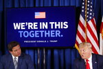 Florida Gov. Ron DeSantis, left, listens as President Donald Trump speaks during a roundtable discussion on the coronavirus outbreak and storm preparedness at Pelican Golf Club in Belleair, Fla., Friday, July 31, 2020. (AP Photo/Patrick Semansky)