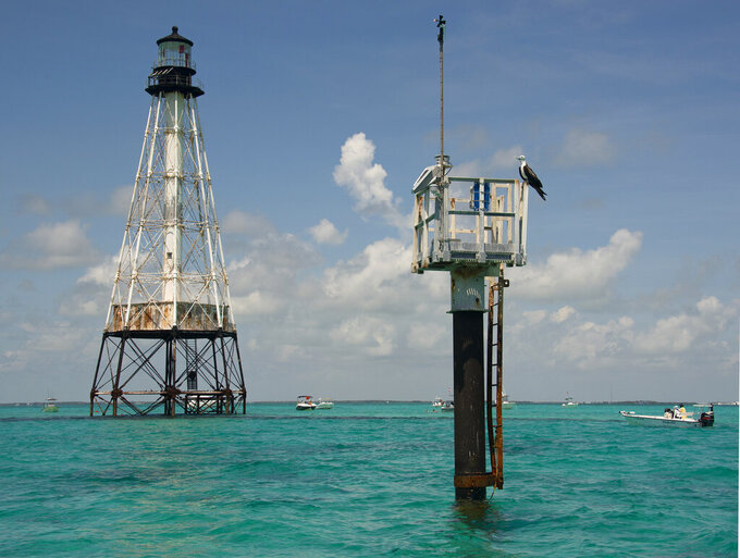 This photo provided by the Florida Keys News Bureau shows boats anchored around Alligator Reef Lighthouse, Tuesday, Sept. 7, 2021, off Islamorada, Fla., in the Florida Keys. On Tuesday, officials from the Islamorada-based Friends of the Pool, Inc., announced that U.S. Secretary of the Interior Deb Haaland approved a recommendation from the National Park Service that the organization be granted ownership of the lighthouse under the National Historic Lighthouse Preservation Act. Friends of the Pool hopes to raise about $9 million to preserve the almost 150-year-old structure. (Andy Newman/Florida Keys News Bureau via AP)