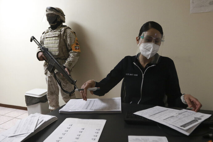 A soldier stands guard as healthcare workers are registered to receive shots of the Pfizer COVID-19 vaccine, on the first day of coronavirus vaccinations in Ciudad Juarez, Mexico, Wednesday, Jan. 13, 2021. (AP Photo/Christian Chavez)