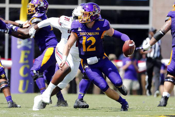 East Carolina's Holton Ahlers (12) runs away from South Carolina's Tonka Hemingway (91) during the first half of an NCAA college football game in Greenville, N.C., Saturday, Sept. 11, 2021. (AP Photo/Karl B DeBlaker)