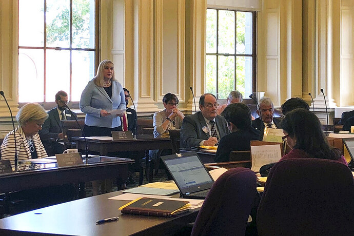 Senate President Donna Soucy, standing left, D-Manchester, speaks in favor of her bill to set New Hampshire's minimum wage, Thursday, Sept. 19, 2019, in the Senate chamber of the Statehouse in Concord, N.H. The Senate voted 14-10 along party lines to override Republican Gov. Chris Sununu's veto of the bill, falling short of the necessary two-thirds majority needed to override. (AP Photo/Holly Ramer)