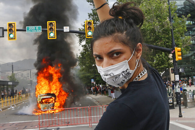 A protester looks on as a flipped over police vehicle burns Saturday, May 30, 2020, in Salt Lake City. People converged on downtown Salt Lake City, Saturday to protest the death of George Floyd who died in Minneapolis police custody on May 25. (AP Photo/Rick Bowmer)