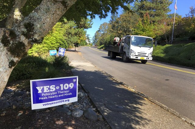 A truck drives past a sign supporting a ballot measure that would legalize controlled, therapeutic use of psilocybin mushrooms, Friday, Oct. 9, 2020 in Salem, Ore. War veterans with PTSD, terminally ill patients and others suffering from anxiety are backing the ballot measure. (AP Photo/Andrew Selsky)
