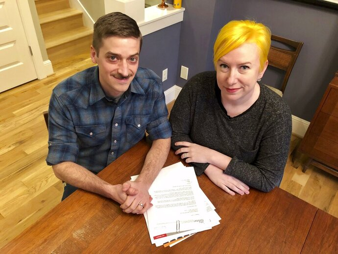 Husband and wife Andy Kraft and Amy Elias, of Portland, Ore., pose with their 2018 tax paperwork in their Portland home on Monday, Feb. 18, 2019. The couple got a small refund last year but this year owe more than $10,000 in taxes under the new tax law. (AP Photo/Gillian Flaccus)