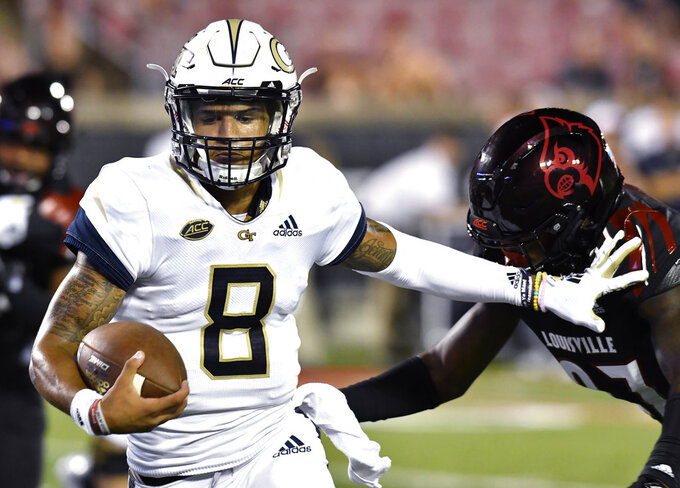 FILE - In this Oct. 5, 2018, file photo, Georgia Tech quarterback Tobias Oliver (8) tries to fend off Louisville linebacker Nick Okeke (97) during the second half of an NCAA college football game in Louisville, Ky. Georgia Tech may continue to alternate quarterbacks TaQuon Marshall and Oliver against Miami on Saturday night. (AP Photo/Timothy D. Easley, File)
