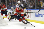 Florida Panthers defenseman Mike Matheson (19) and Vegas Golden Knights center Nicolas Roy (10) chase the puck during the first period of an NHL hockey game, Thursday, Feb. 6, 2020, in Sunrise, Fla. (AP Photo/Lynne Sladky)