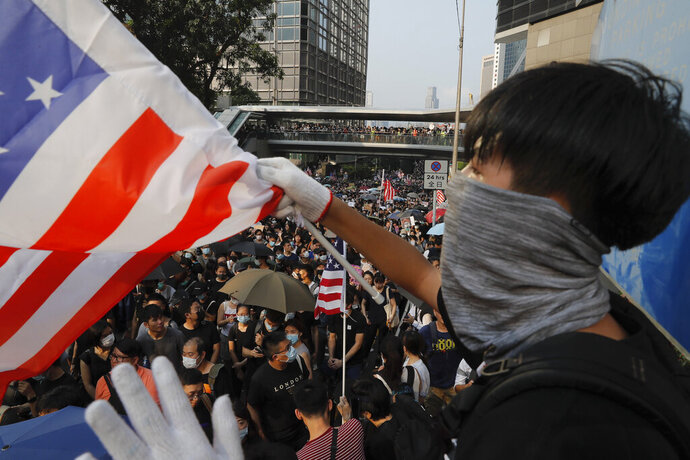 """A protester waves a U.S. flag in Hong Kong, Sunday, Sept. 8, 2019. Thousands of demonstrators in Hong Kong urge President Donald Trump to """"liberate"""" the semi-autonomous Chinese territory during a peaceful march to the U.S. consulate, but violence broke out later in the business and retail district after protesters vandalized subway stations, set fires and blocked traffic. (AP Photo/Kin Cheung)"""
