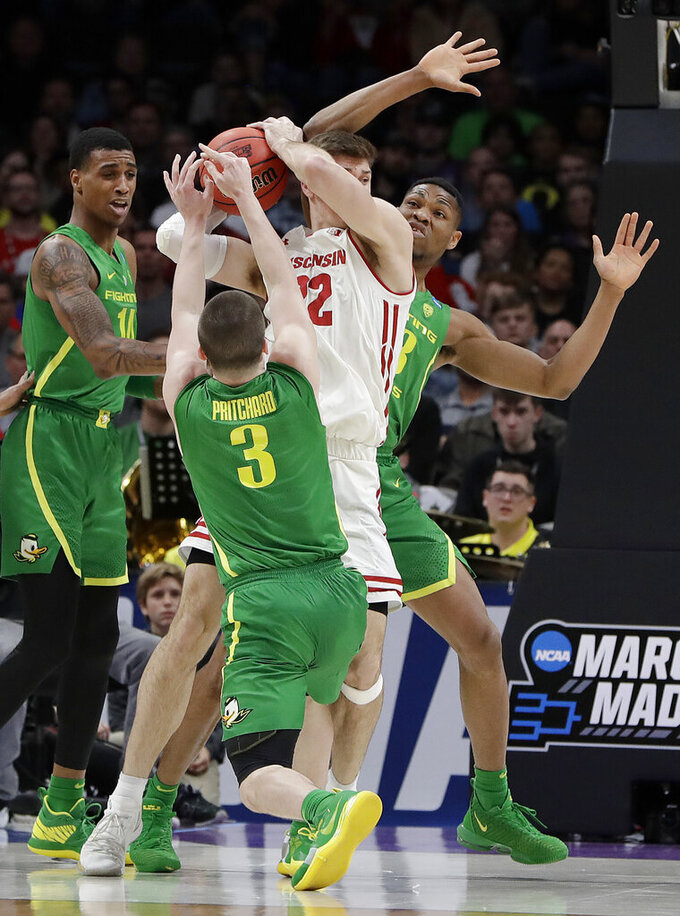 Wisconsin forward Ethan Happ, center, looks to pass while surrounded by Oregon guard Payton Pritchard (3), forward Francis Okoro, right, and forward Kenny Wooten (14) during the first half of a first round men's college basketball game in the NCAA Tournament, Friday, March 22, 2019, in San Jose, Calif. (AP Photo/Chris Carlson)