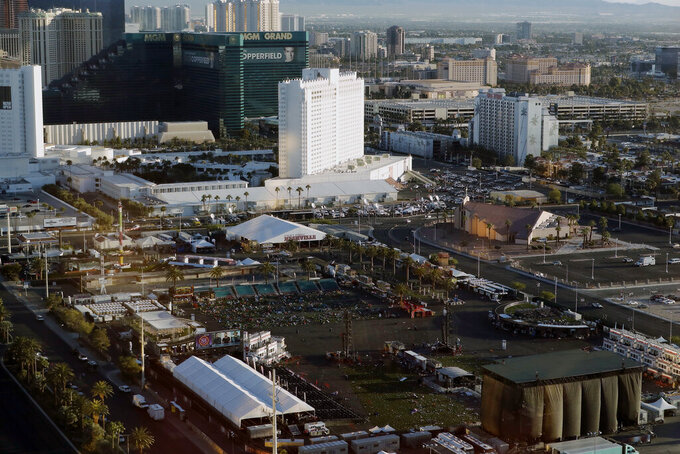 FILE - In this Oct. 3, 2017, file photo, debris litters a festival grounds across the street from the Mandalay Bay resort and casino following a mass shooting in Las Vegas. The casino company that owns the former Las Vegas Strip concert venue that became the site of the deadliest mass shooting in modern American history said Monday, Aug. 2, 2021, it is donating part of the property for a permanent memorial. (AP Photo/Marcio Jose Sanchez, File)