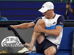 Australia's John Millman changes his socks during a break in his third round match against Switzerland's Roger Federer at the Australian Open tennis championship in Melbourne, Australia, Friday, Jan. 24, 2020. (AP Photo/Lee Jin-man)
