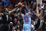 Miami Heat forward Jimmy Butler (22) goes to the basket as Los Angeles Clippers forward Kawhi Leonard (2) and guard Landry Shamet (20) defend during the first half of an NBA basketball game, Friday, Jan. 24, 2020, in Miami. (AP Photo/Lynne Sladky)