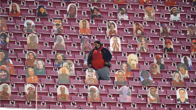 A man walks past cardboard cutouts during the second half of an NCAA college football game between Oregon State and Utah Saturday, Dec. 5, 2020, in Salt Lake City. (AP Photo/Rick Bowmer)