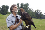 """Jack Hubley holds a golden eagle at The Falconry Experience July 8, 2021, in Hershey, Pa. Hubley spends his days educating people about birds of prey through """"The Falconry Experience"""" at the Hotel Hershey, part of the Hersheypark resort. He's a master falconer who can hunt with hawks and eagles, and he also holds a federal falconry education permit. (Brian Whipkey/Daily American via AP)"""