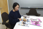 """In this Jan. 23, 2019, photo, Park Jiehyun, features director at Cosmopolitan Korea, watches fashion magazine during an interview in Seoul, South Korea. South Korea has the world's highest ratio of plastic surgeons per capita, according to a report by the International Society of Plastic Surgery in 2016. According to 2015 statistics by Gallup Korea, about one third of South Korean women between 19 and 29 said they've had plastic surgery. """"I think (South Korean women) want to look perfect,"""" said Park Jiehyun, features director at Cosmopolitan Korea, a popular fashion magazine. """"They believe they should have a nice body and skin, beautiful eyes, nose and mouth, and even sleek hair with a perfect hairline. They also want to have good style.""""  But Park says rising feminist movements and changing values among South Korean women are redirecting her industry's depiction of beauty. (AP Photo/Jung Yoon Kim)park"""