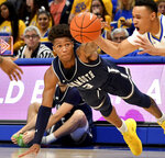 Monmouth guard Deion Hammond reaches for a loose ball against Pitt guard Trey McGowens in the first half of an NCAA college basketball game Monday, Nov. 18, 2019, in Pittsburgh, Pa. (Matt Freed/Pittsburgh Post-Gazette via AP)