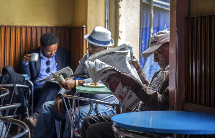 FILE - In this Monday, Oct. 10, 2016 file photo, Ethiopian men read newspapers and drink coffee at a cafe during a declared state of emergency and internet shurdown in Addis Ababa, Ethiopia. Ethiopian lawmakers on Thursday, Feb. 13, 2020 approved a controversial law aimed at curbing hate speech and disinformation just months ahead of a major election but some worry the new law will restrict freedom of expression in a country that once jailed thousands of people, including journalists, over political views. (AP Photo/Mulugeta Ayene, File)
