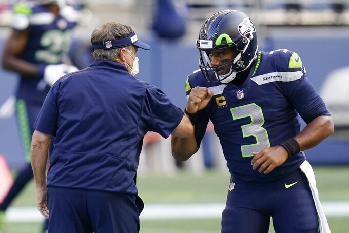New England Patriots head coach Bill Belichick, left, greets Seattle Seahawks quarterback Russell Wilson, right, before an NFL football game, Sunday, Sept. 20, 2020, in Seattle. (AP Photo/Elaine Thompson)