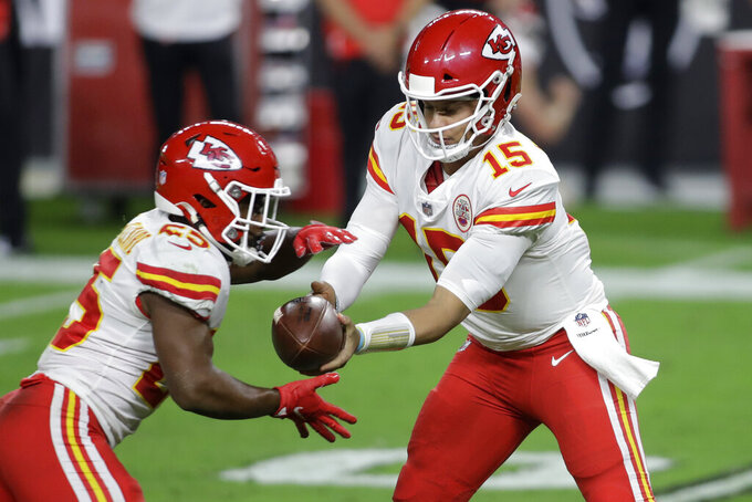 Kansas City Chiefs quarterback Patrick Mahomes (15) hands the ball off to running back Clyde Edwards-Helaire (25) during the first half of an NFL football game against the Las Vegas Raiders, Sunday, Nov. 22, 2020, in Las Vegas. (AP Photo/Isaac Brekken)