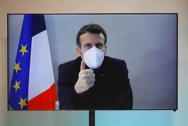 French President Emmanuel Macron is seen on a screen as he attends by video conference a round table for the National Humanitarian Conference (NHC), taken at the Foreign Ministry in Paris,Thursday, Dec. 17, 2020. French President Emmanuel Macron tested positive for COVID-19 Thursday following a week in which he met with numerous European leaders. The French and Spanish prime ministers and EU Council president were among many top officials self-isolating because they had recent contact with him. (Charles Platiau/Pool via AP)