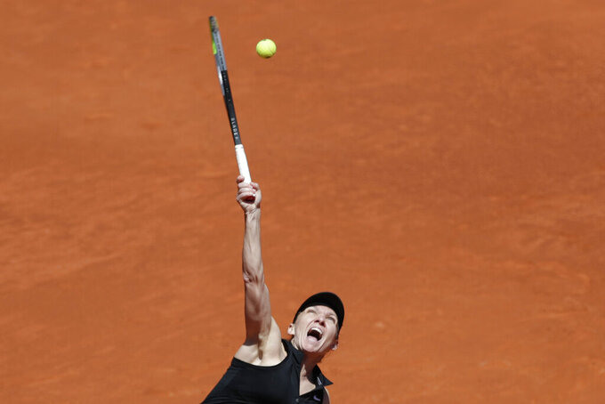 Simona Halep of Romania serves to Elise Mertens of Belgium during their match at the Madrid Open tennis tournament in Madrid, Spain, Tuesday, May 4, 2021. (AP Photo/Paul White)