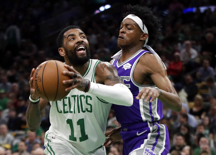 Boston Celtics guard Kyrie Irving (11) drives against Sacramento Kings guard De'Aaron Fox in the first half of an NBA basketball game, Thursday, March 14, 2019, in Boston. (AP Photo/Elise Amendola)
