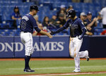 Tampa Bay Rays' Daniel Robertson, right, shakes hands with third base coach Matt Quatraro after Robertson hit a home run off Texas Rangers starting pitcher Martin Perez during the fourth inning of a baseball game Monday, April 16, 2018, in St. Petersburg, Fla. (AP Photo/Chris O'Meara)