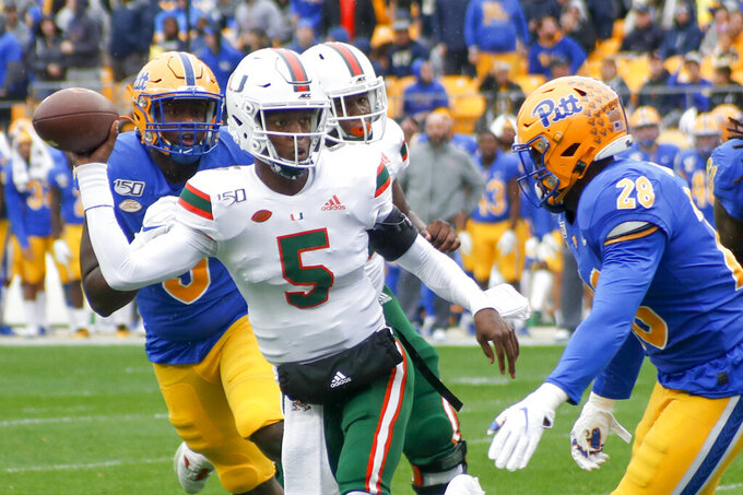 Miami quarterback N'Kosi Perry (5) looks to pass as he scrambles away from Pittsburgh linebacker Kylan Johnson (28) during the first half of an NCAA college football game, Saturday, Oct. 26, 2019, in Pittsburgh. (AP Photo/Keith Srakocic)