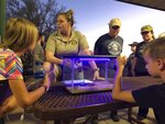 This Aug. 18, 2019 photo shows Park Ranger Anna Roberts, center, talking about scorpions and how to catch them in Lost Dutchman State Park, Ariz. Feared, admired and loathed, scorpions have roamed the earth for 450 million years. An interesting way to learn about the critters, which glow under black lights, is to go on scorpion hunts in Southwest states like Arizona and New Mexico. Wear closed-toed shoes and pants, bring black lights and prepare to be awed. (AP Photo/Peter Prengaman)