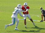 Miami Dolphins quarterback Tua Tagovailoa (1) hands the ball off to Miami Dolphins running back Kalen Ballage (27) during an NFL football training camp practice in Davie, Fla., Tuesday, Aug. 18, 2020. (AP Photo/Joel Auerbach)