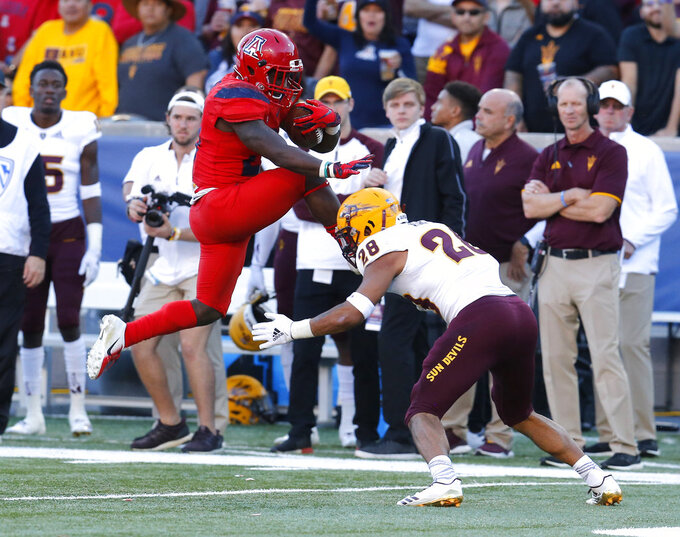 Arizona running back J.J. Taylor tries to leap over Arizona State defensive back Demonte King (28) in the second half during an NCAA college football game, Saturday, Nov. 24, 2018, in Tucson, Ariz. (AP Photo/Rick Scuteri)