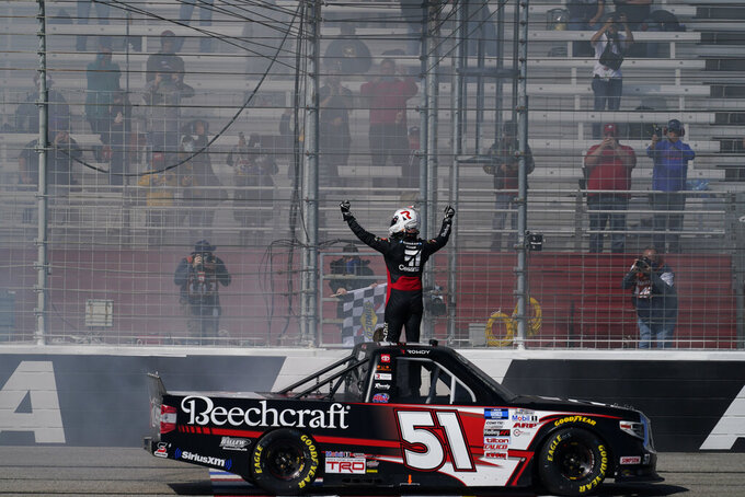 NASCAR driver Kyle Busch celebrates after he wins a NASCAR Camping World Truck Series race at Atlanta Motor Speedway on Saturday, March 20, 2021, in Hampton, Ga. (AP Photo/Brynn Anderson)