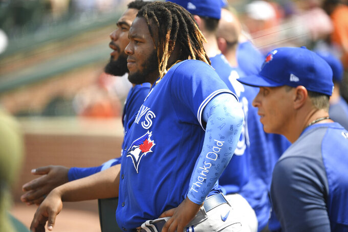 """Toronto Blue Jays Vladimir Guerrero Jr. looks on from the dugout while wearing an arm sleeve with the words """"Thanks Dad"""" inscribed on it during a baseball game against the Baltimore Orioles, Sunday, June 20, 2021, in Baltimore. (AP Photo/Terrance Williams)"""