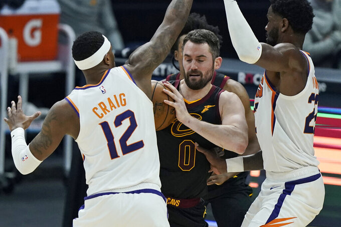 Cleveland Cavaliers Kevin Love, center, tries to get past Phoenix Suns' Torrey Craig, left, and Deandre Ayton, right, in the first half of an NBA basketball game, Tuesday, May 4, 2021, in Cleveland. (AP Photo/Tony Dejak)