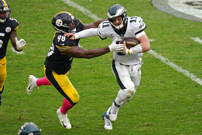 Philadelphia Eagles quarterback Carson Wentz (11) scrambles out of the pocket under pressure by Philadelphia Eagles defensive tackle Hassan Ridgeway (98) during the second half of an NFL football game, Sunday, Oct. 11, 2020, in Pittsburgh. (AP Photo/Keith Srakocic)