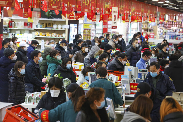 Shoppers wearing face masks pay for their groceries at a supermarket in Wuhan in central China's Hubei province, Saturday, Jan. 25, 2020. The virus-hit Chinese city of Wuhan, already on lockdown, banned most vehicle use downtown and Hong Kong said it would close schools for two weeks as authorities scrambled Saturday to stop the spread of an illness that is known to have infected more than 1,200 people and killed 41, according to officials.  (Chinatopix via AP)
