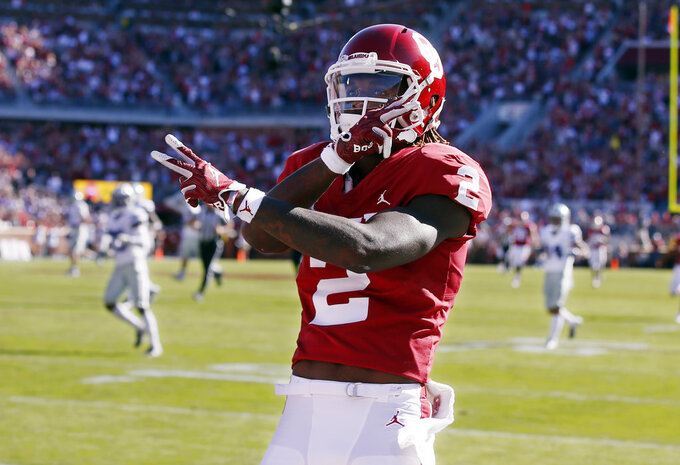 FILE - In this Oct. 27, 2018, file photo, Oklahoma wide receiver CeeDee Lamb (2) celebrates a touchdown during an NCAA college football game against Kansas State in Norman, Okla. Oklahoma quarterback Kyler Murray has star receivers in Marquise Brown and Lamb, yet he doesn't hesitate to throw to other options.(AP Photo/Sue Ogrocki, File)