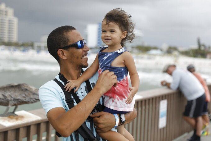 """Michael Taylor, also known as the """"The Armed Fisherman"""" strapped with his assault rifle and hand gun shares a moment with his daughter, Ocean while at Pier 60 on Clearwater Beach, Fla., on July 3, 2021. (Octavio Jones/Tampa Bay Times via AP)"""