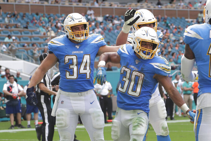 Los Angeles Chargers fullback Derek Watt (34) and offensive guard Michael Schofield (75) congratulate running back Austin Ekeler (30) after Ekeler scored a touchdown, during the second half at an NFL football game against the Miami Dolphins, Sunday, Sept. 29, 2019, in Miami Gardens, Fla. (AP Photo/Lynne Sladky)