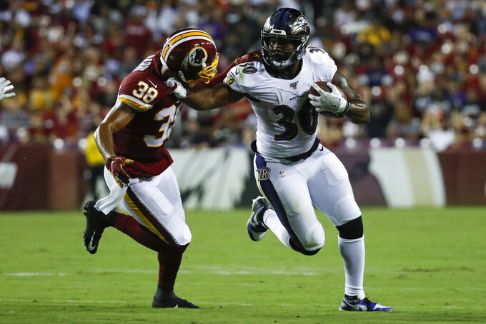 Baltimore Ravens running back Kenneth Dixon (30) tries to get away from Washington Redskins defensive back Deion Harris (38) during the first half of an NFL preseason football game Thursday, Aug. 29, 2019, in Landover, Md. (AP Photo/Alex Brandon)