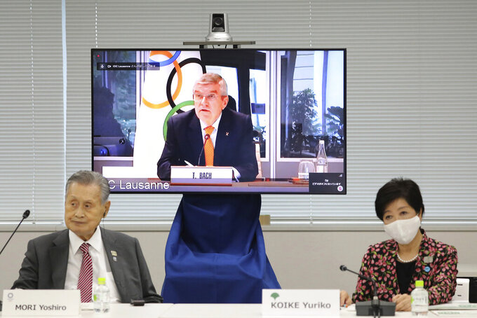 "In this Sept. 24, 2020, file photo, IOC President Thomas Bach, on the screen, speaks remotely with Tokyo 2020 Organizing Committee President Yoshiro Mori, left, and Tokyo Gov. Yuriko Koike, right, during an on-line meeting focused on how to pull off the delayed Tokyo Games, in Tokyo. The IOC and local organizers are trying to ""simplify"" next year's postponed Tokyo Olympics, promising to save money in what one study says is already the most expensive Summer Olympics on record. (Du Xiaoyi/Pool Photo via AP)"