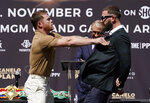 Unified WBC/WBO/WBA super middleweight champion Canelo Alvarez, left, shoves undefeated IBF Super Middleweight Champion Caleb Plant during a news conference Tuesday, Sept. 21, 2021, in Beverly Hills, Calif., to announce their 168-pound title bout. The fight is scheduled for Saturday, Nov. 6 in Las Vegas. (AP Photo/Mark J. Terrill)