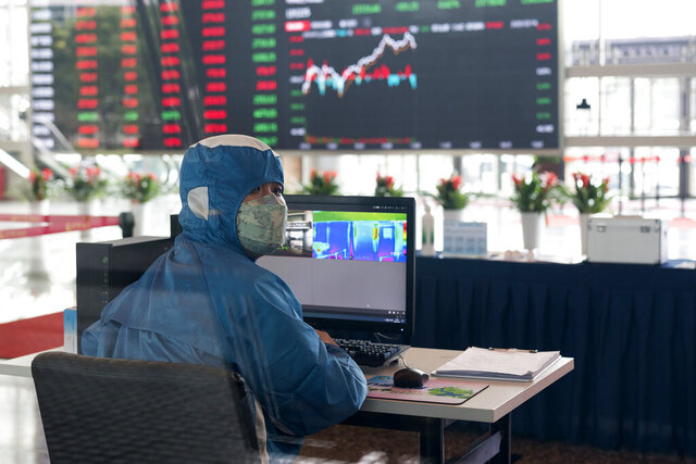 A worker wearing a protective suit reacts in front of an infrared temperature machine in the lobby of the Shanghai Stock Exchange building in Shanghai, China, Friday, Feb. 14, 2020. Asian shares mostly fell Friday as investors turned cautious following a surge in cases of a new virus in China that threatens to crimp economic growth and hurt businesses worldwide. (AP Photo)
