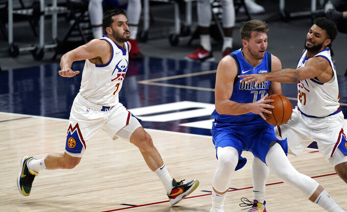 Dallas Mavericks guard Luka Doncic, center, is defended by Denver Nuggets guard Facundo Campazzo, left, and guard Jamal Murray during the first half of an NBA basketball game Saturday, March 13, 2021, in Denver. (AP Photo/David Zalubowski)