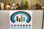 FILE - In this Nov. 1, 2016, file photo, agents help sign people up for insurance through the Covered California exchange at their storefront in Huntington Beach, Calif. Individual insurance premiums on California's health exchange for the uninsured will go up 1.8% on average next year, a low increase credited to record enrollment and increased competition among health carriers, officials announced Wednesday, July 28, 2021. (Nick Agro/The Orange County Register via AP, File)