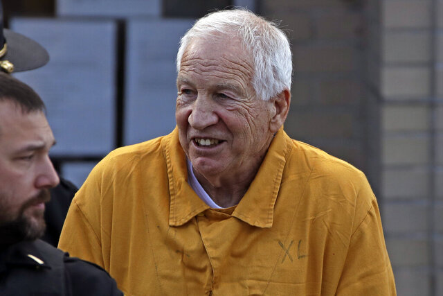 Former Penn State University assistant football coach Jerry Sandusky, center, leaves the Centre County Courthouse after attending a resentencing hearing on his 45-count child sexual abuse conviction Friday, Nov. 22, 2019. (AP Photo/Gene J. Puskar)