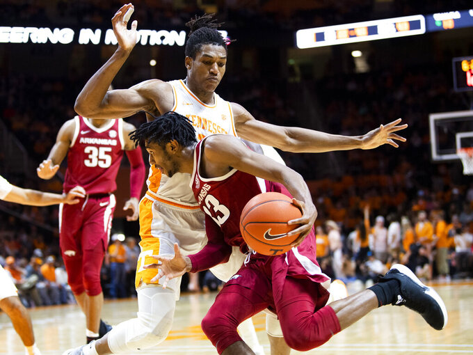 Tennessee guard/forward Yves Pons (35) defends Arkansas guard Jimmy Whitt Jr. (33) during an NCAA college basketball game, Tuesday, Feb. 11, 2020 in Knoxville, Tenn. (Brianna Paciorka/Knoxville News Sentinel via AP)
