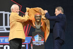 Cliff Harris, left, a member of the Pro Football Hall of Fame Centennial Class,  and his presenter, Charlie Waters, unveil the bust of Harris during the induction ceremony at the Pro Football Hall of Fame, Saturday, Aug. 7, 2021, in Canton, Ohio. (AP Photo/David Richard)